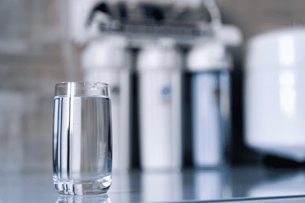 A water filtration system and a glass of purified water.